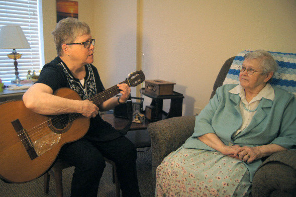 Sister Mary Susan Dewitt plays for a resident in the Memory Care haven at Benedictine Living Community of Duluth